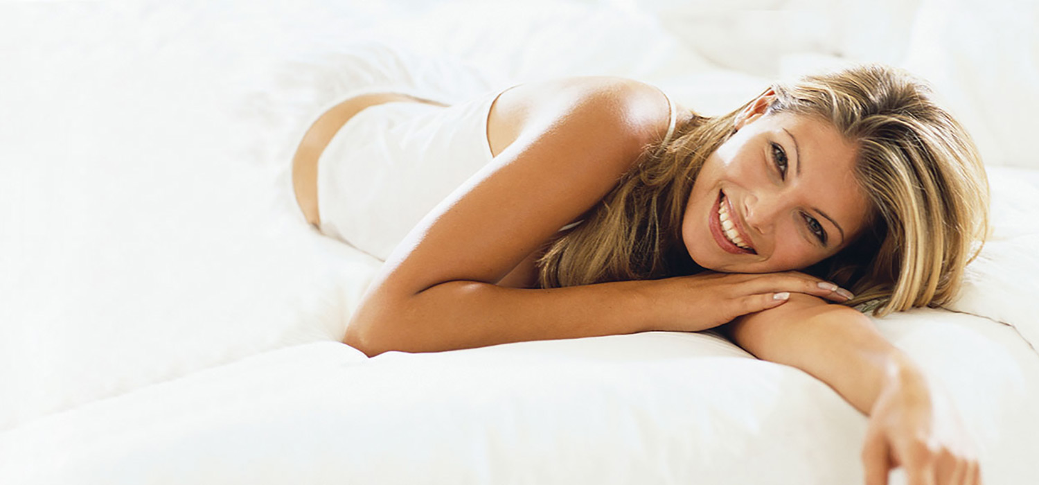 Woman smiling while laying on her side on a mattress with white sheets